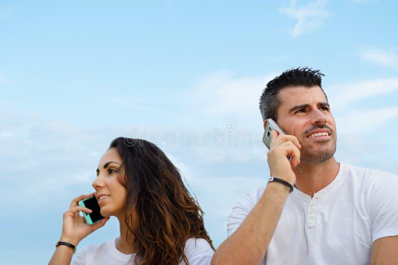 Man en vrouw bij het spreken op cellphones tegen hemelachtergrond royalty-vrije stock afbeeldingen