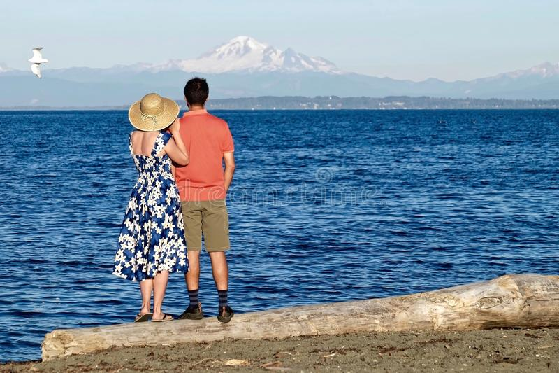 Man en vrouw bij strand het koesteren stock afbeelding