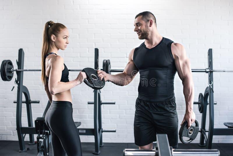 Man en vrouw in de gewichten van de sportkledingsholding in gymnastiek royalty-vrije stock fotografie