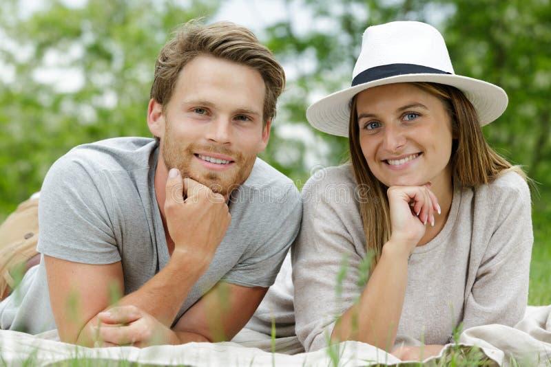 Man en vrouw die bij gras het stellen liggen stock afbeelding