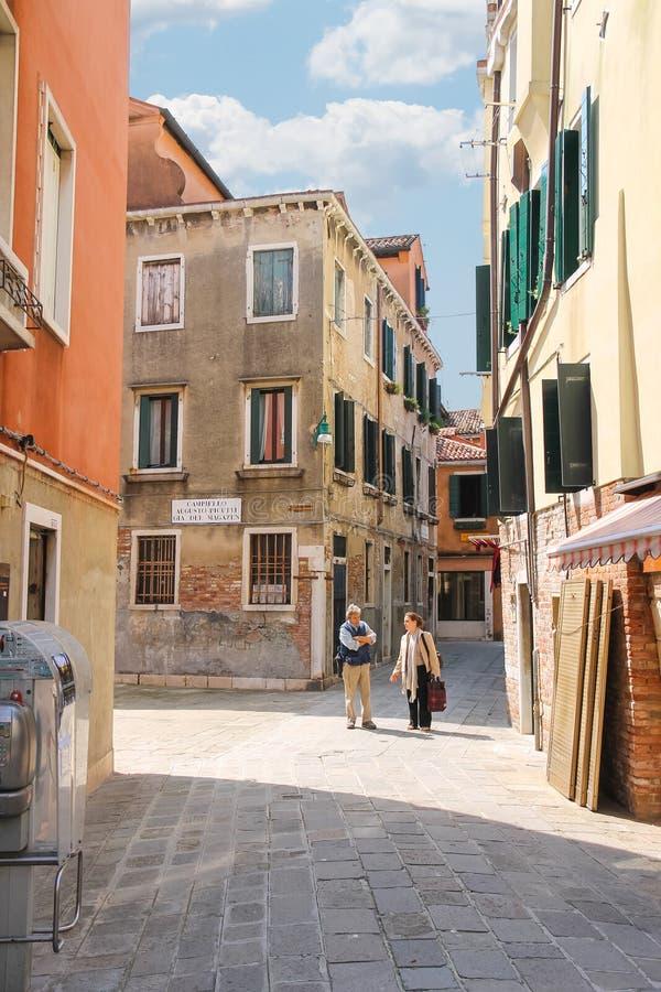 Man en vrouw die bij kruispunten in Venetië, Italië spreken royalty-vrije stock afbeeldingen