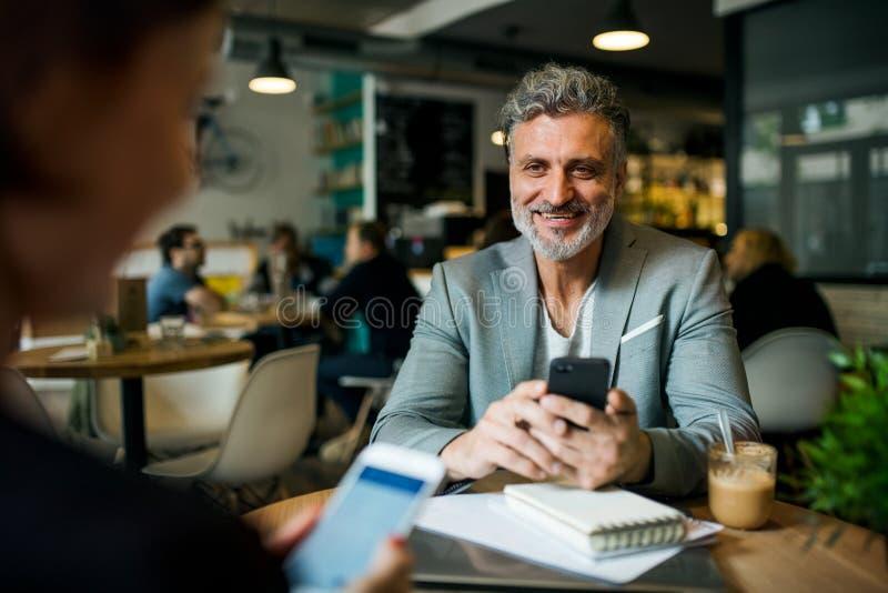 Man en vrouw die commerciële vergadering in een koffie hebben, die smartphones gebruiken stock afbeelding