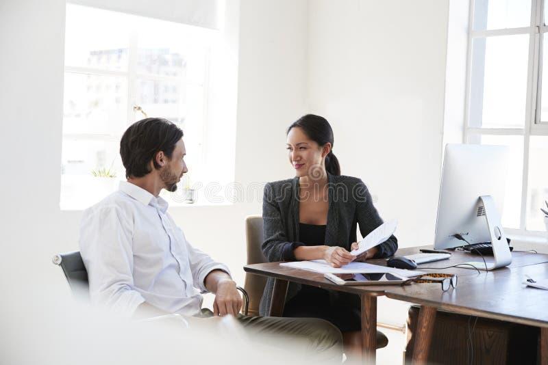 Man en vrouw die documenten bespreken bij een bureau in een bureau stock foto's