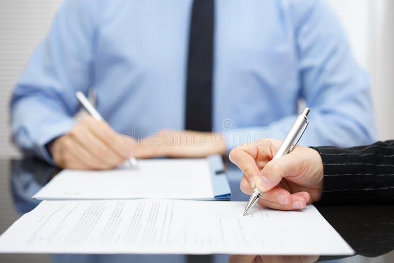 Man en vrouw die een bedrijfscontract na de conclusie ondertekenen royalty-vrije stock afbeelding
