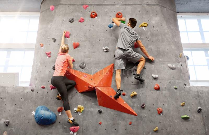 Man en vrouw die een muur beklimmen bij binnengymnastiek royalty-vrije stock afbeeldingen