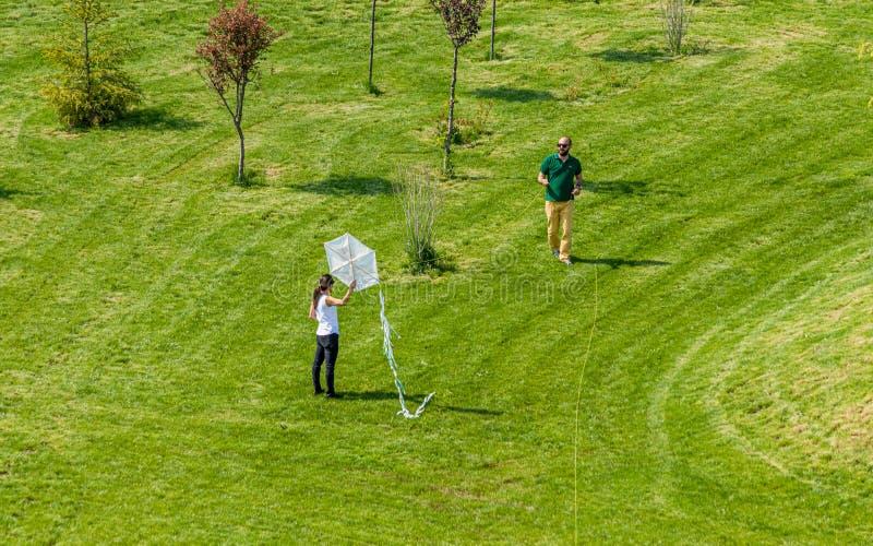 Man en vrouw die een witte vlieger in een park vliegen stock foto's