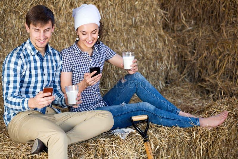Man en vrouw die en van verse melk babbelen genieten stock afbeelding