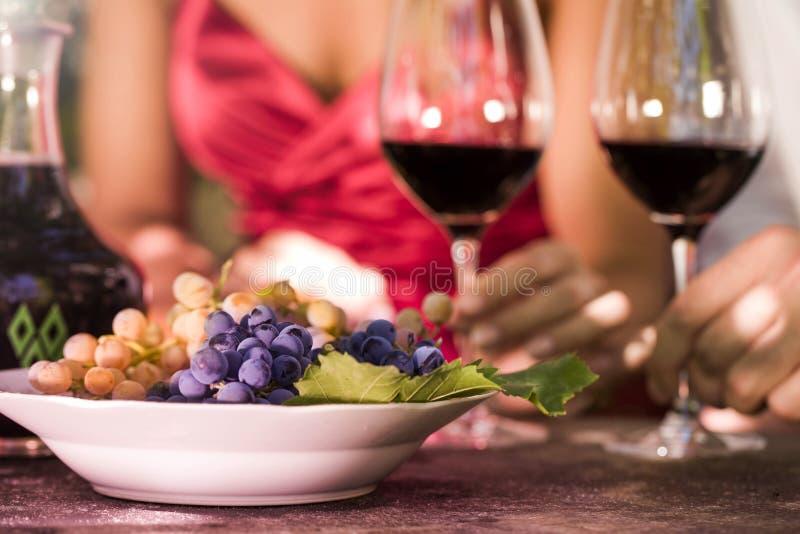 Man en vrouw die gelezen wijn drinken en druiven eten stock foto's