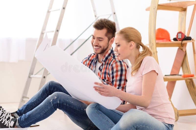 Man en vrouw die hun huisplan bekijken royalty-vrije stock afbeeldingen