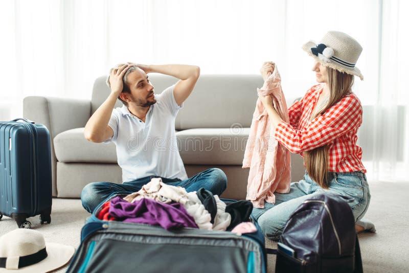 Man en vrouw die hun koffers voor vakantie inpakken royalty-vrije stock afbeelding