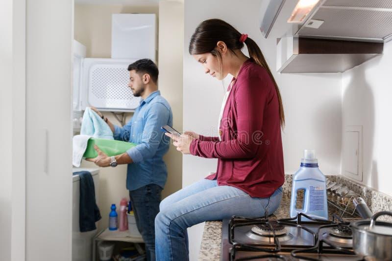 Man en Vrouw die Karweien doen die Kleren wassen stock fotografie