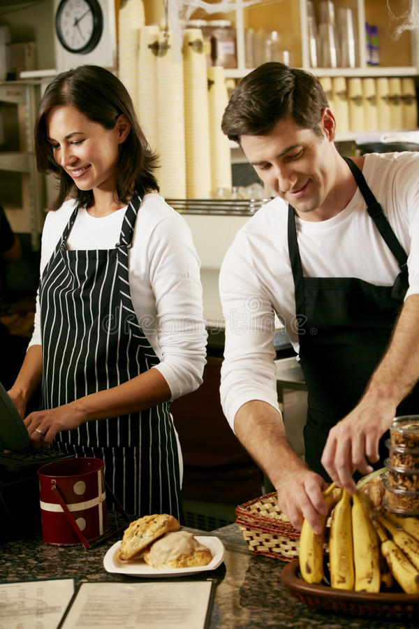 Man en Vrouw die in koffiewinkel werken stock foto's