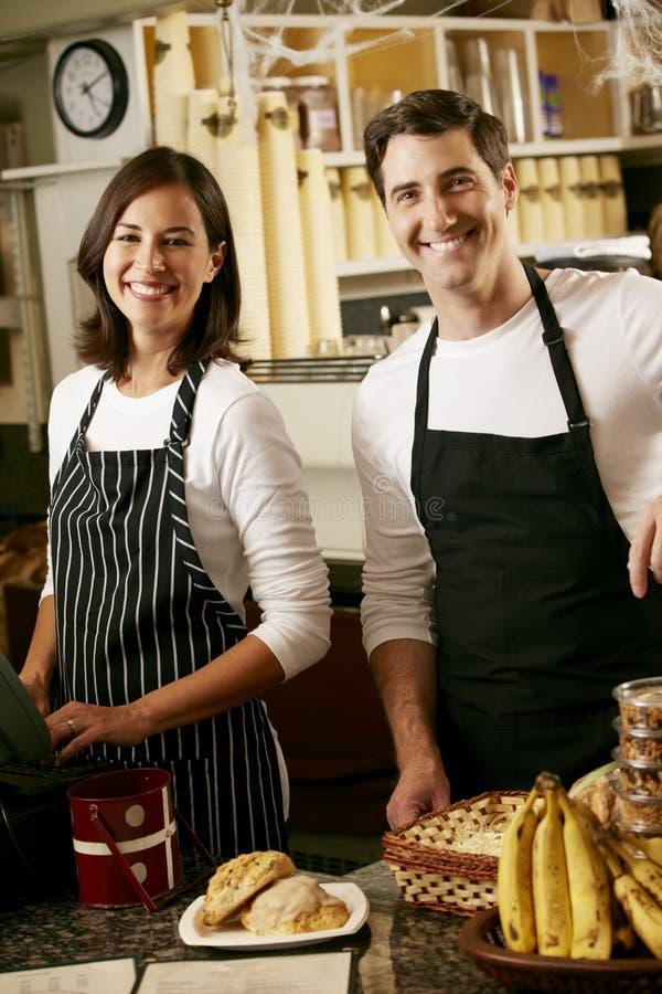 Man en Vrouw die in koffiewinkel werken stock foto