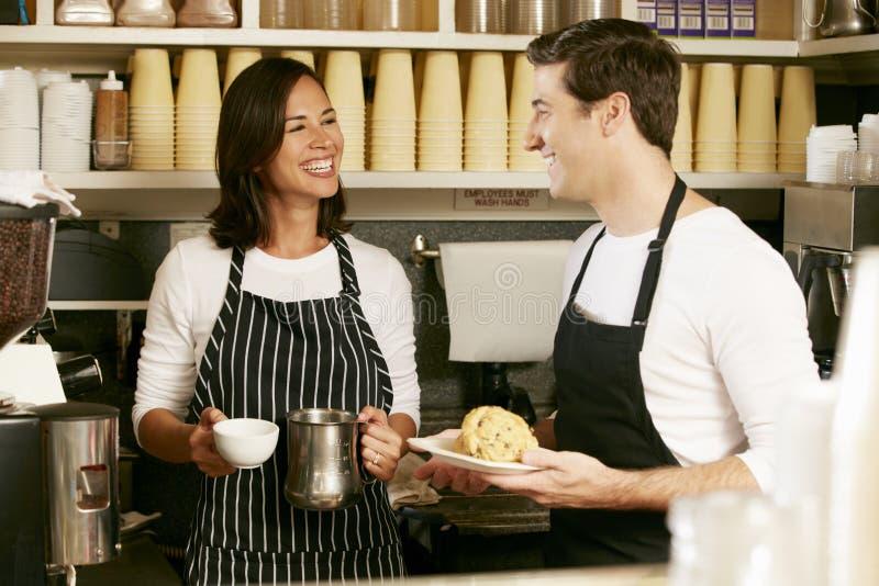 Man en Vrouw die in koffiewinkel werken stock fotografie