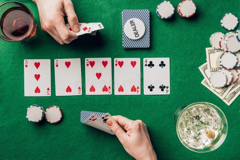 Man en vrouw die met kaarten pook spelen door lijst met dranken stock foto