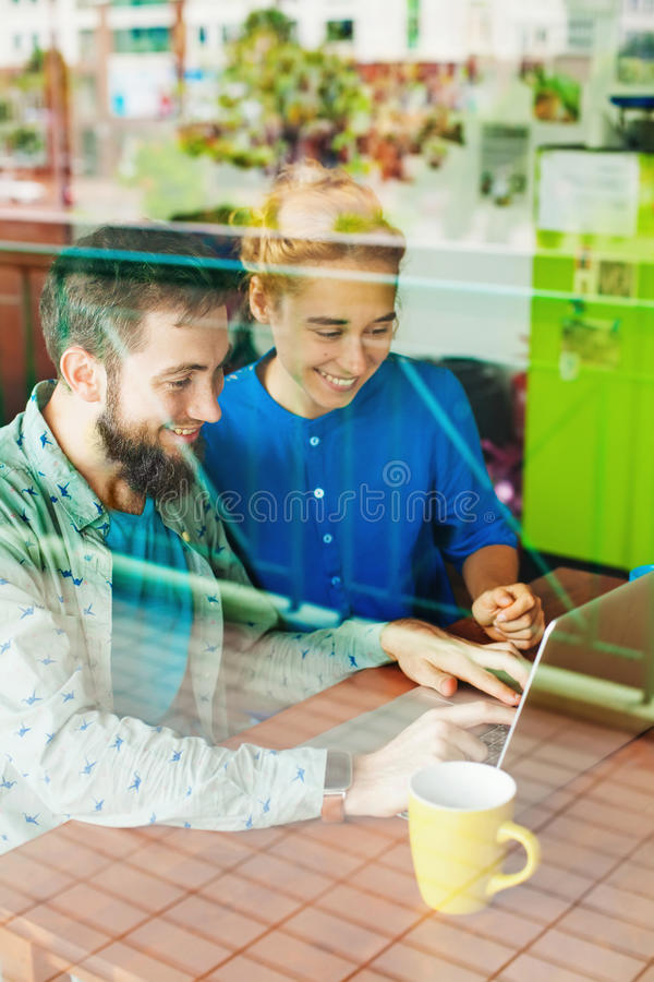 Man en vrouw die met laptop samenwerken stock fotografie