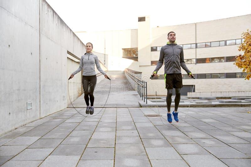 Man en vrouw die met springtouw in openlucht uitoefenen stock afbeelding