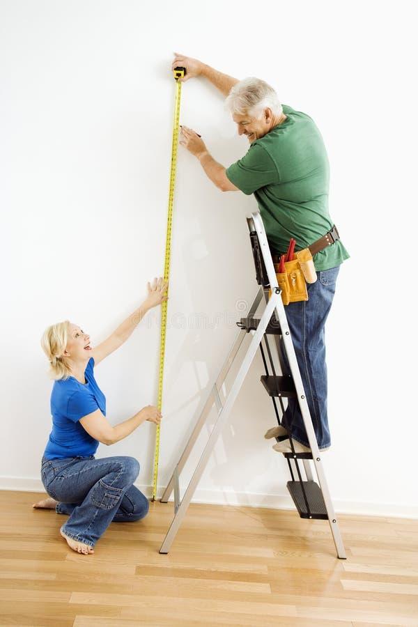 Man en vrouw die muur meten. royalty-vrije stock foto