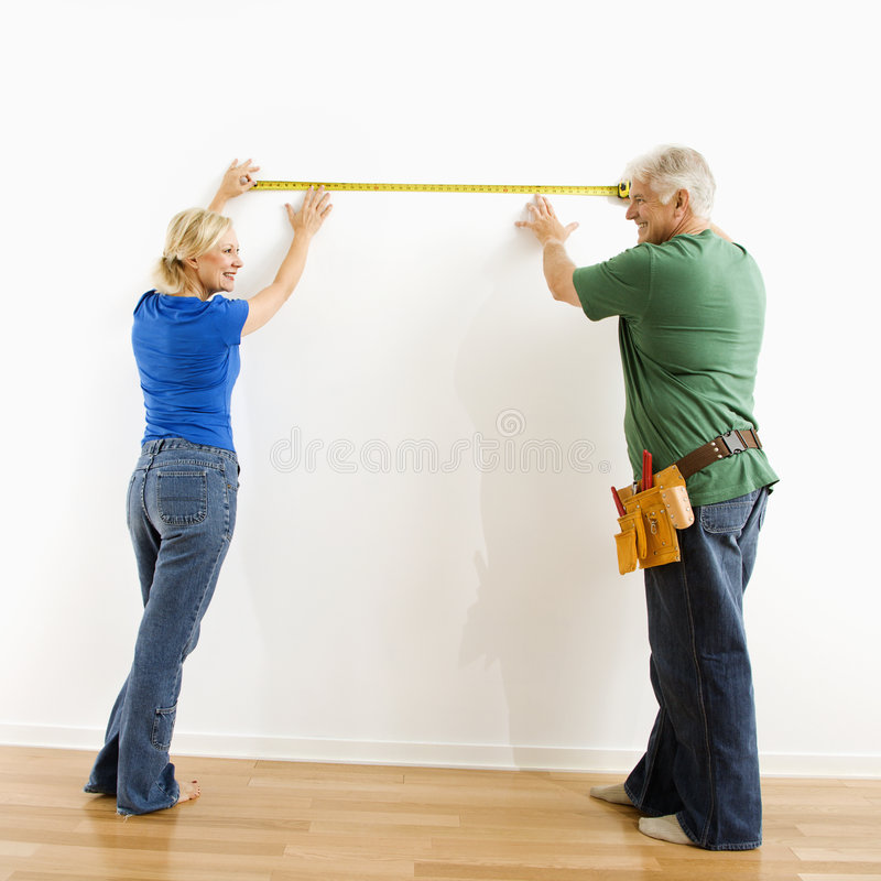 Man en vrouw die muur meten. stock foto