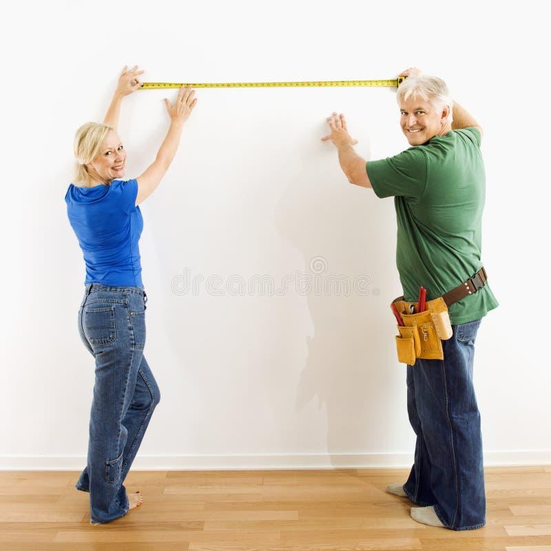 Man en vrouw die muur meten. stock foto's