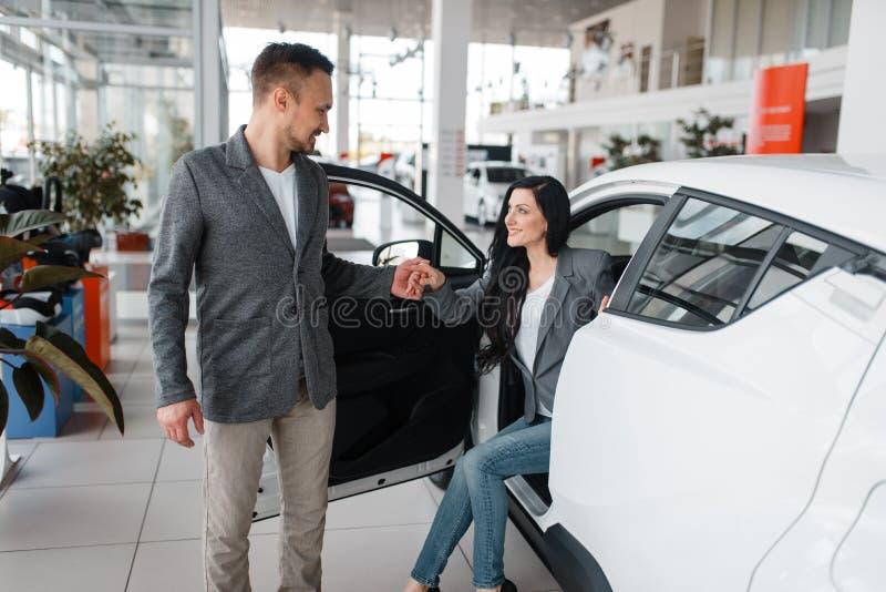 Man en vrouw die nieuwe auto in toonzaal kopen royalty-vrije stock foto's