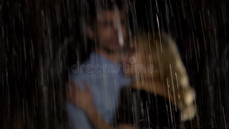 Man en vrouw die onder de regen koesteren en op taxi, romantische datum wachten stock foto's