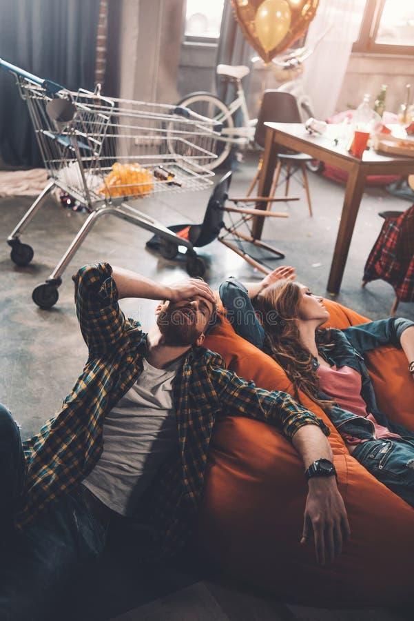Man en vrouw die op beanbagstoel rusten in slordige ruimte na partij royalty-vrije stock foto