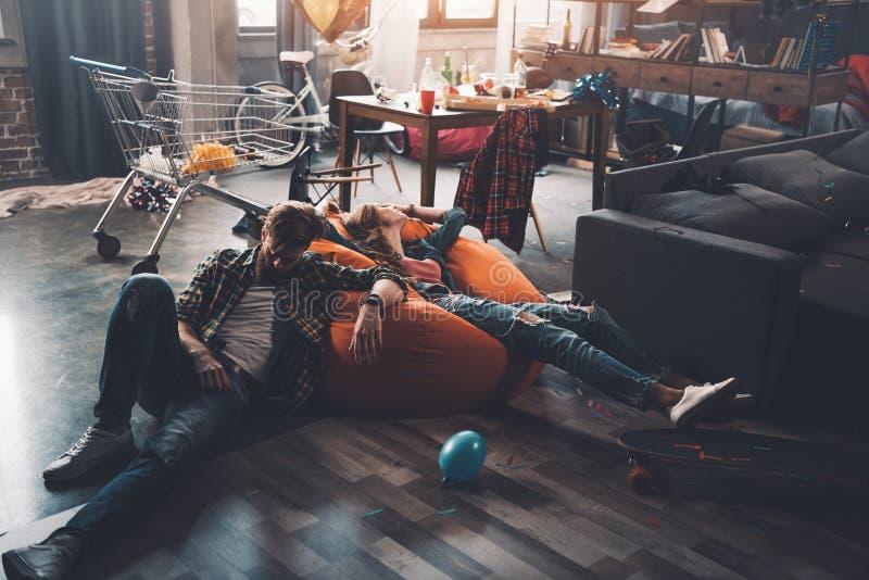 Man en vrouw die op beanbagstoel rusten in slordige ruimte na partij royalty-vrije stock afbeelding