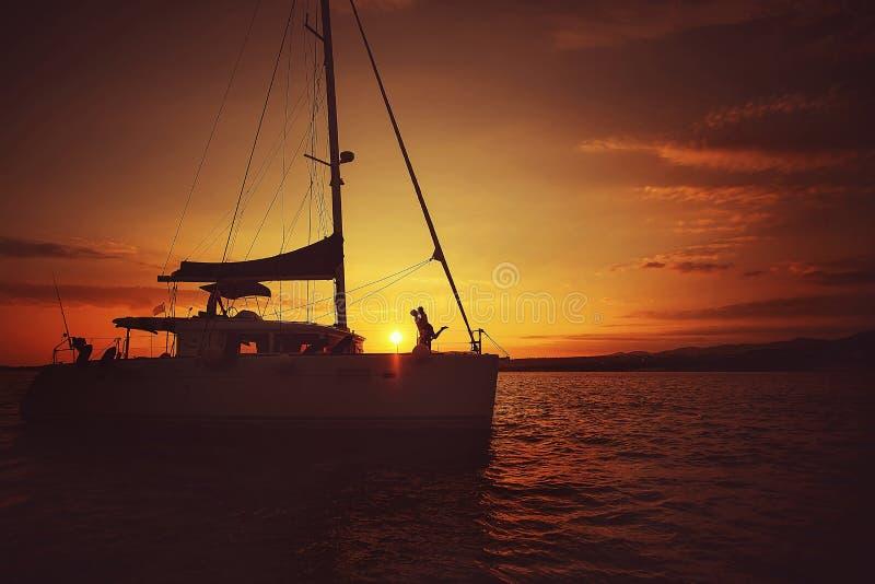 Man en vrouw die op een jacht bij zonsondergang koesteren royalty-vrije stock afbeeldingen