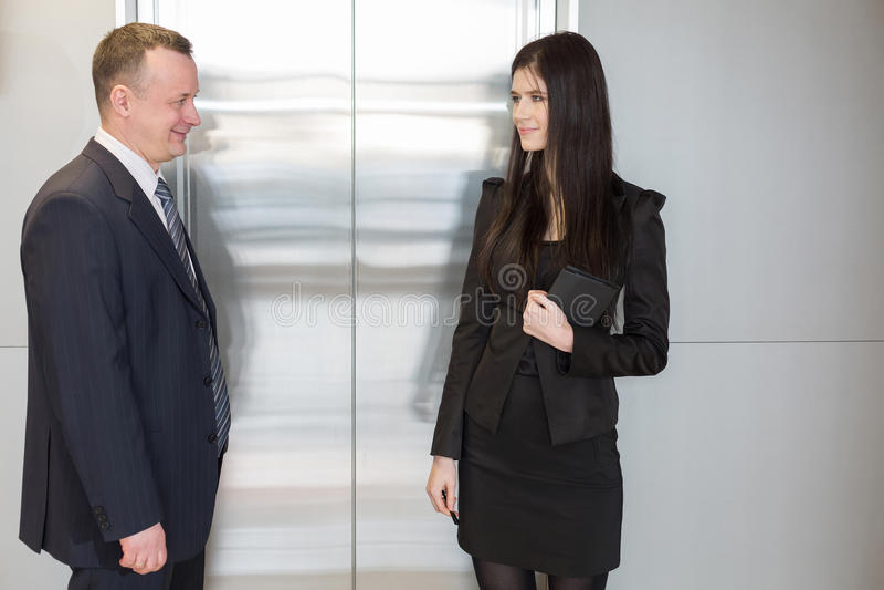 Man en vrouw die op lift wachten royalty-vrije stock afbeelding