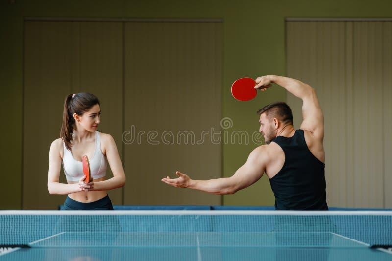 Man en vrouw die op pingpong binnen opleiden royalty-vrije stock foto