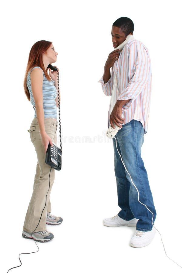 Man en Vrouw die op Telefoons spreken stock afbeelding