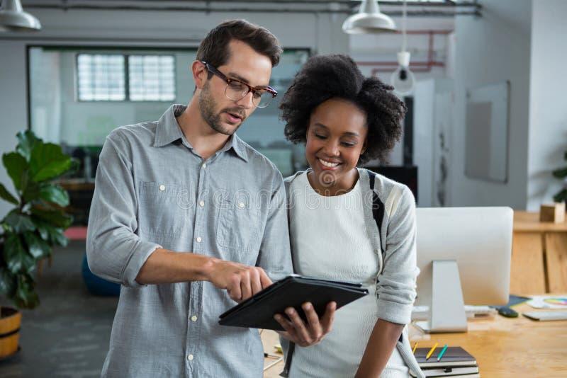 Man en vrouw die over digitale laptop bespreken stock afbeelding