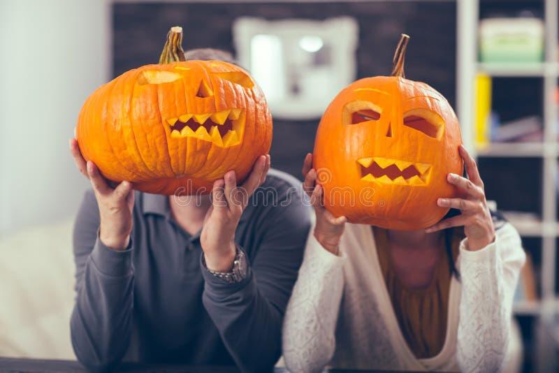 Man en vrouw die pret met Halloween-pompoen hebben stock fotografie