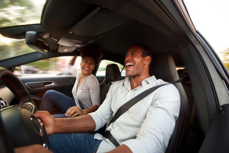 Man en vrouw die en samen in auto glimlachen zitten stock foto