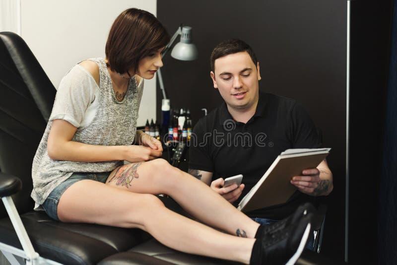 Man en vrouw die tatoegeringsontwerp in studio kiezen stock afbeelding