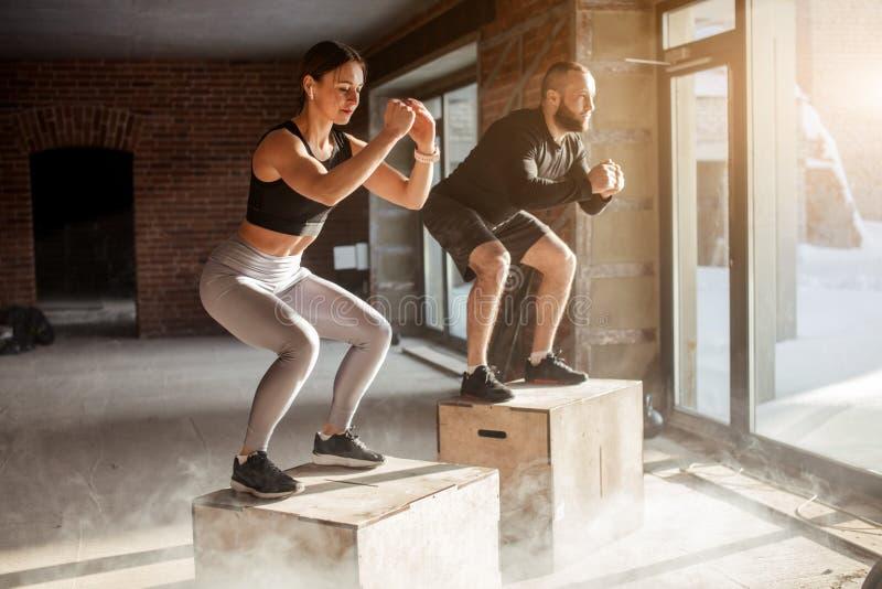Man en vrouw die tohether op dozen in gymnastiek, funcrionaltraining voor mensen springen stock fotografie