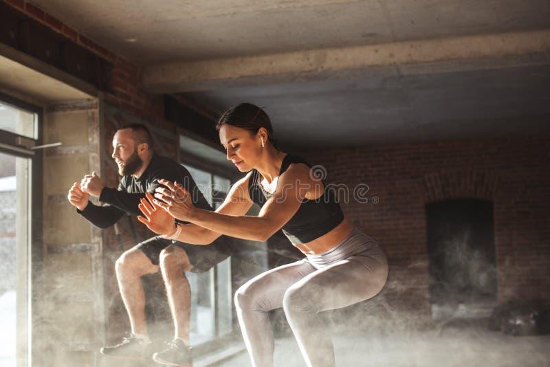 Man en vrouw die tohether op dozen in gymnastiek, funcrionaltraining voor mensen springen royalty-vrije stock afbeelding