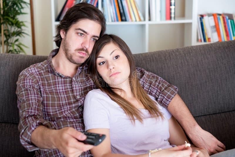 Man en vrouw die TV-op film op de bank letten stock foto
