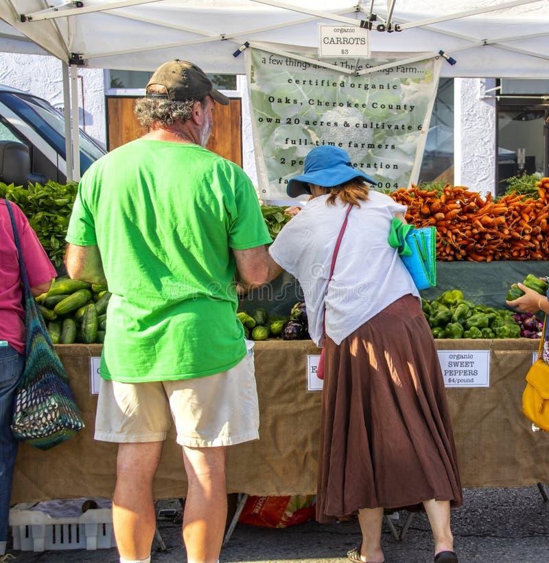 Man en vrouw die voor groenten in Cherry Street Farmers Market winkelen royalty-vrije stock foto's