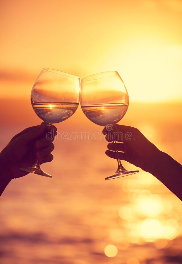 Man en vrouw die wijnglazen met champagne klinken bij zonsondergang royalty-vrije stock foto's