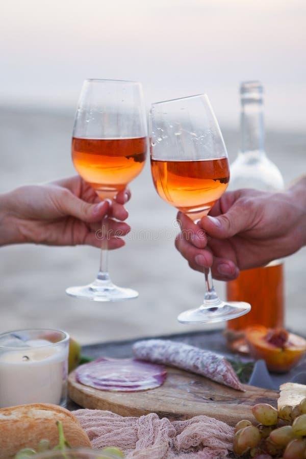 Man en vrouw die wijnglazen met roze wijn klinken bij zonsondergangbea royalty-vrije stock foto