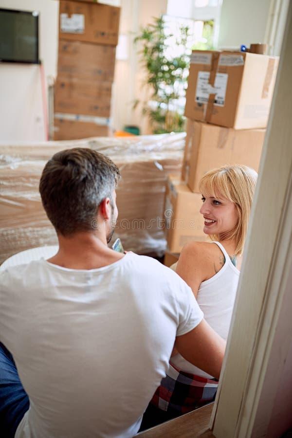 Man en vrouw die zich in nieuw huis bewegen Het zitten op vloer en het ontspannen na het uitpakken stock fotografie