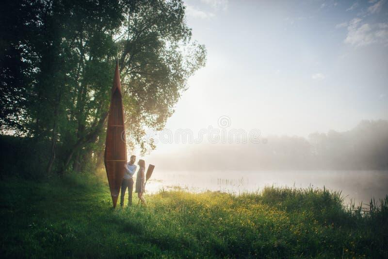 Man en vrouw die zich op kust van meer bevinden stock afbeelding