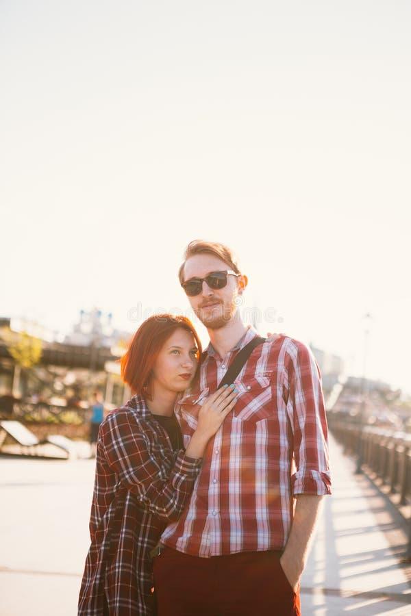 Man en vrouw in het plaidoverhemd die op de achtergrond van de stad koesteren royalty-vrije stock foto's