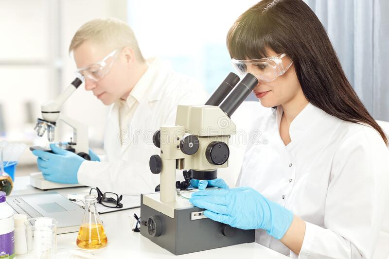 Man en vrouw kijken door een microscoop royalty-vrije stock afbeelding