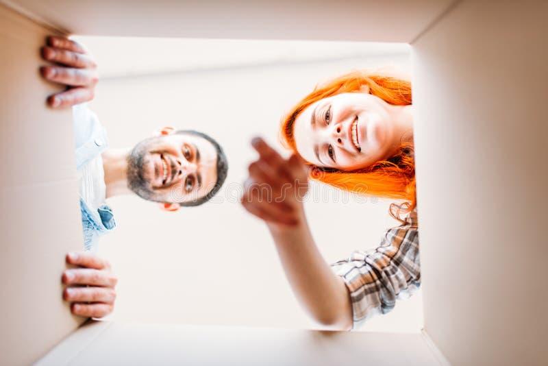 Man en vrouw, mening van binnenuit de kartondoos stock afbeeldingen