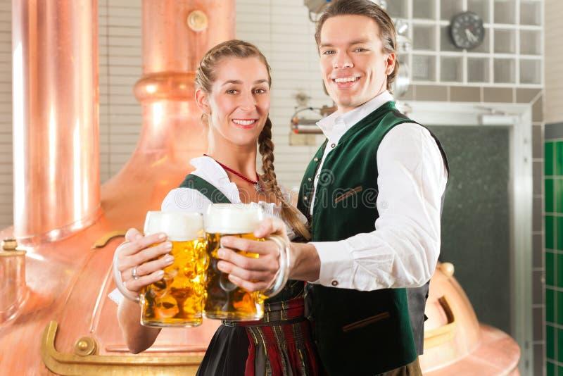 Man en vrouw met bierglas in brouwerij stock foto's
