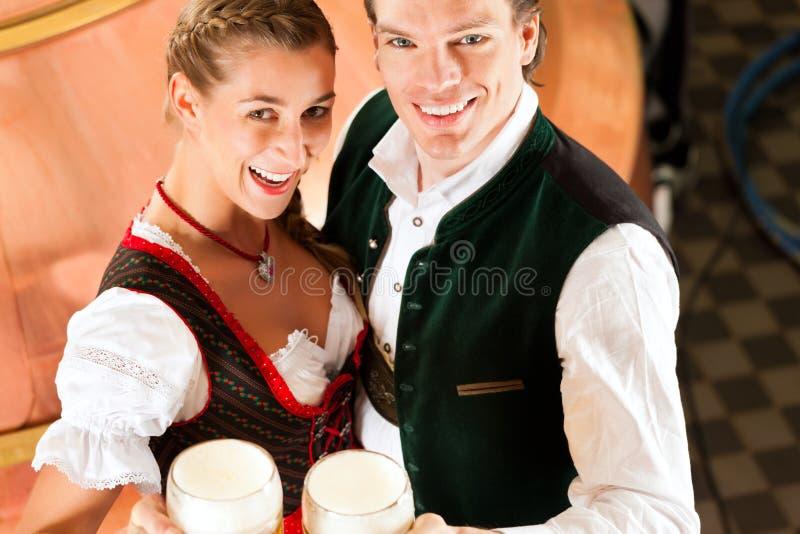 Man en vrouw met bierglas in brouwerij stock afbeeldingen