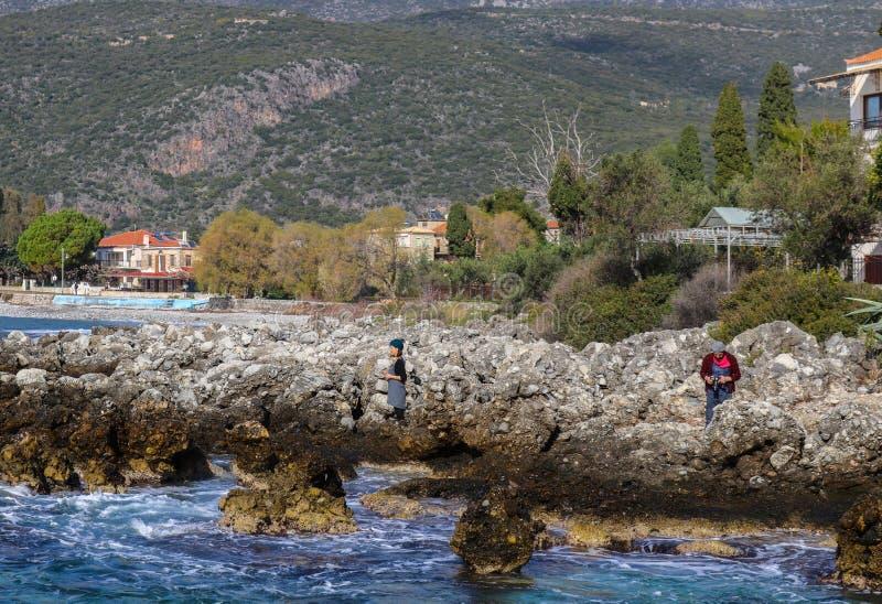 Man en vrouw met camera in rotsen neer door de oceaan in Kardamyli-dorp op het Schiereiland van de Peloponnesus in Griekenland 1  royalty-vrije stock foto